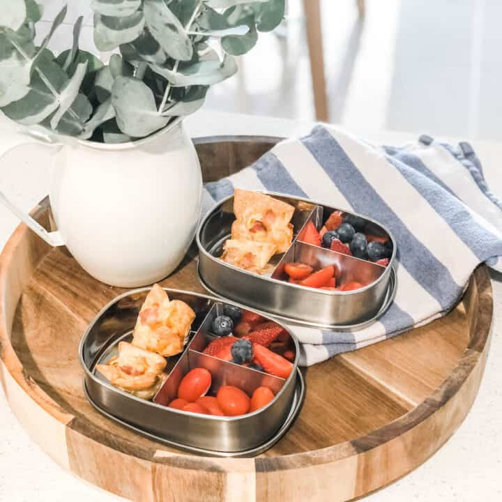 Photo showing two bento-style stainless steel lunchboxes with strawberries and blueberries inside on a round wooden tray next to a enamel pitcher with eucalyptus leaves and a blue and white striped tea towel