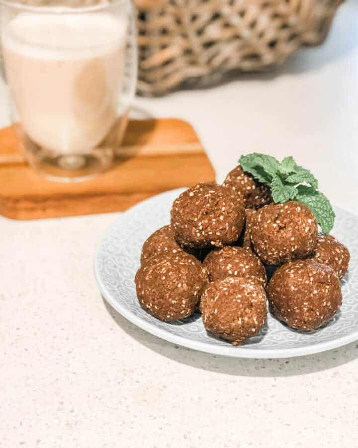 Image showing pile of chocolate bliss balls on a small blue plate with a sprig of mint garnish and a coffee in the background