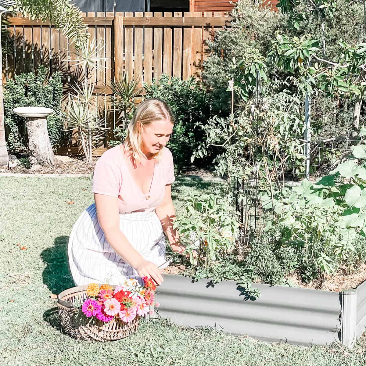 Photo of Emily kneeling by a raised garden bed next to a basket of flowers