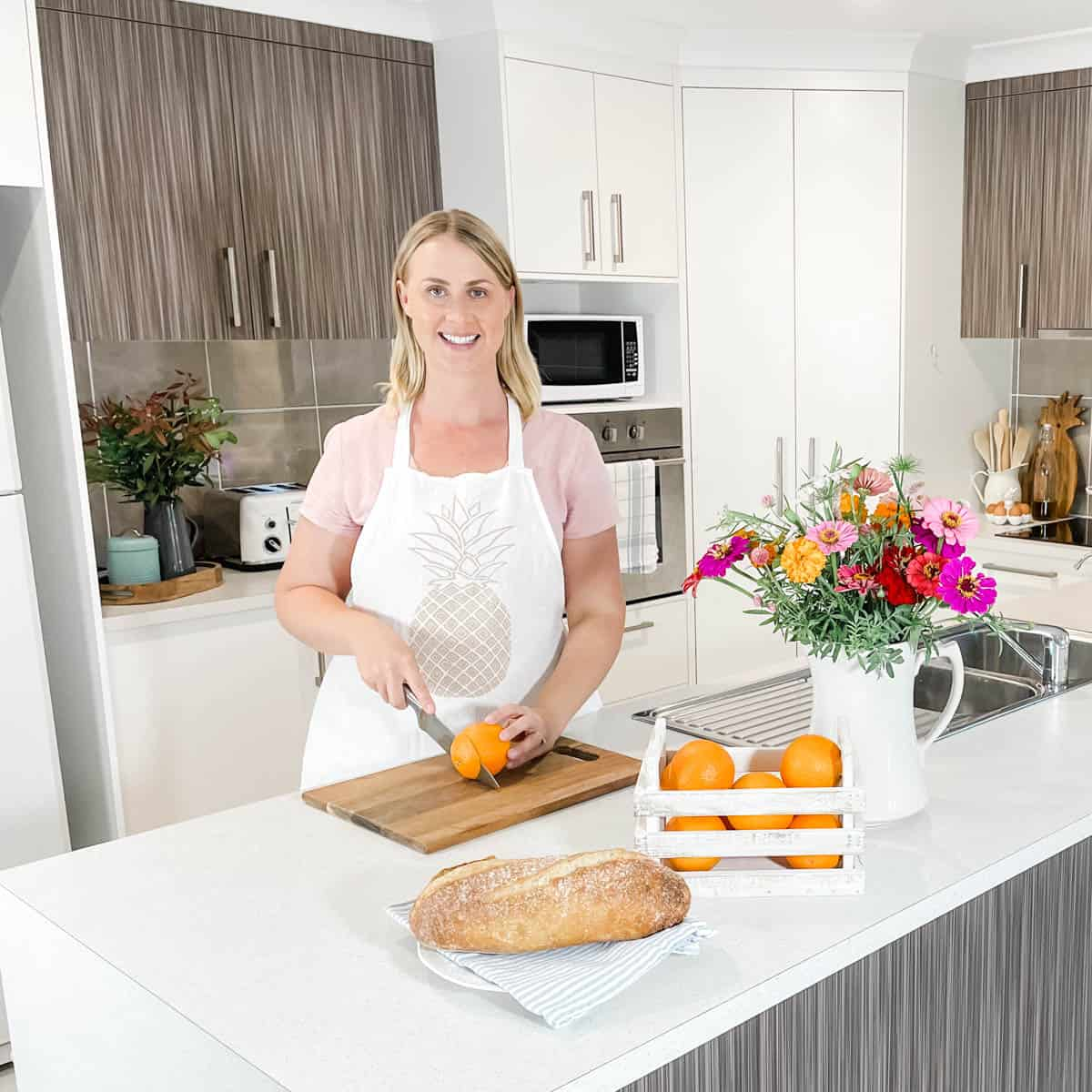 Image of Emily in the kitchen slicing an orange with a knife on a wooden chopping board