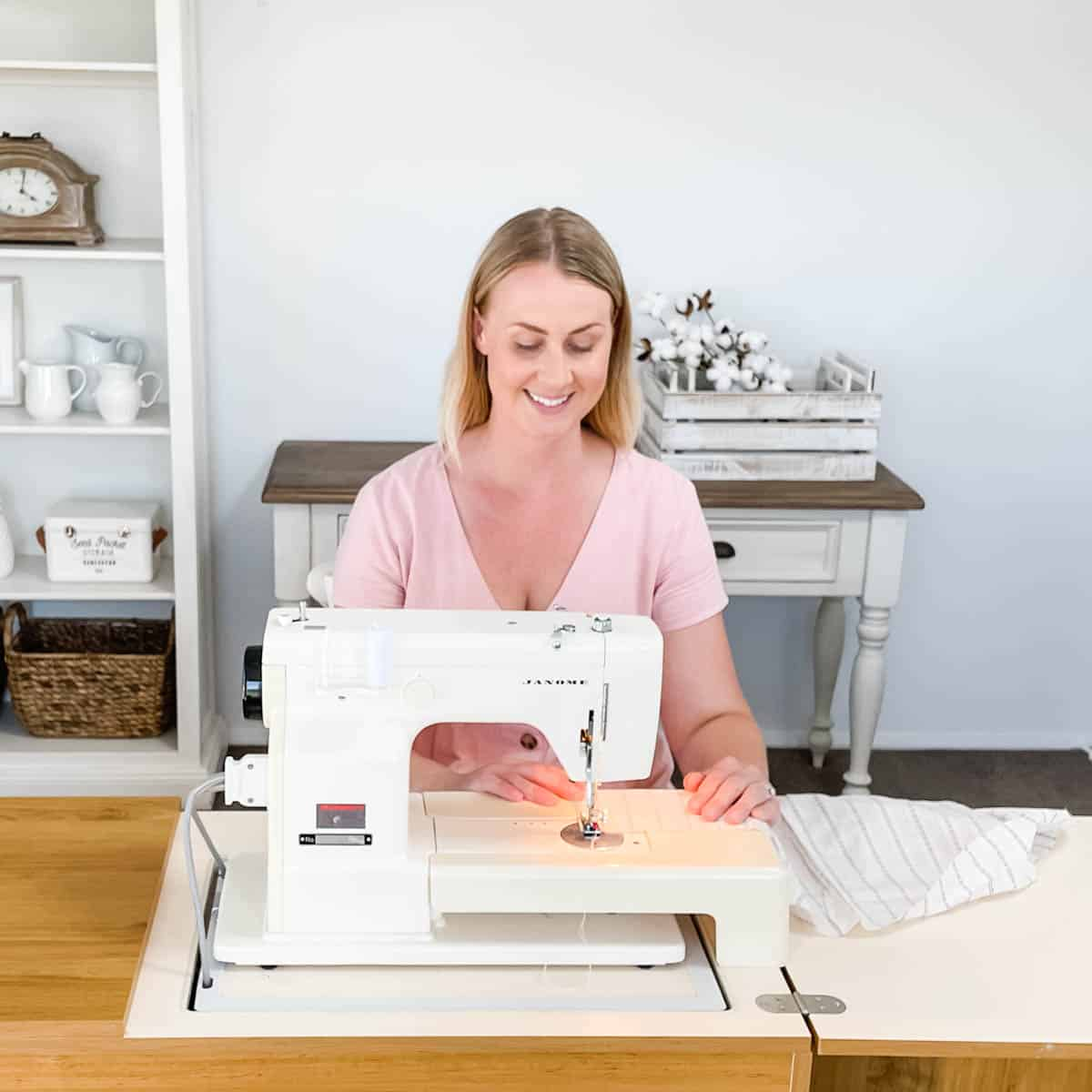 Image of Emily sitting at the sewing machine sewing white and blue striped fabric