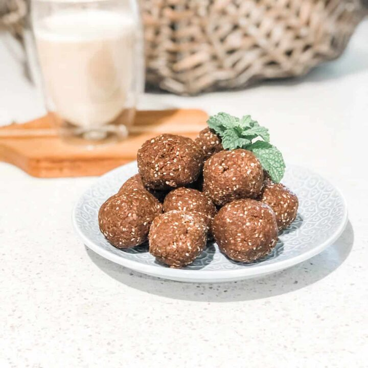 photo of pile of chocolate bliss balls on a blue plate with a cup of coffee in the background