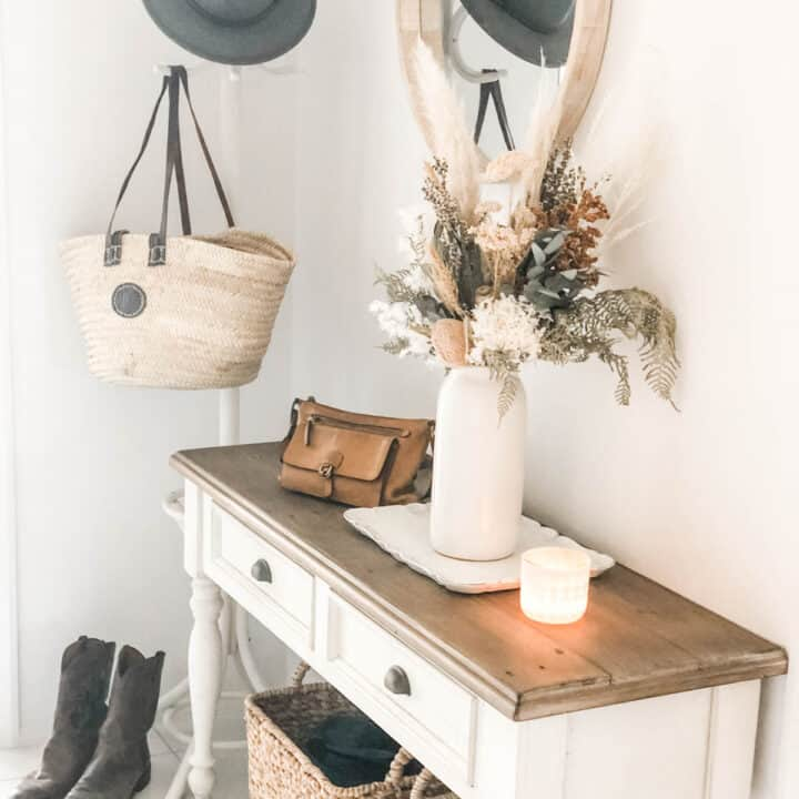 Image of a hallway with a console table, dried floral arrangement in a vase, hat stand with bag and hat hanging on it, woven baskets under the table, a pair of boots, handbag and candle