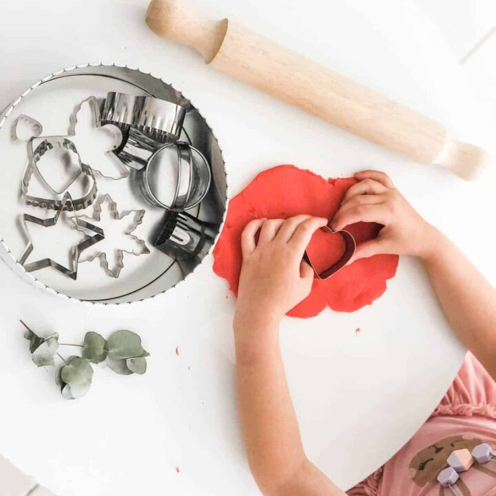 Image of child's arms and red play dough rolled out on small white table next to wooden rolling pin and tin with cookie cutters
