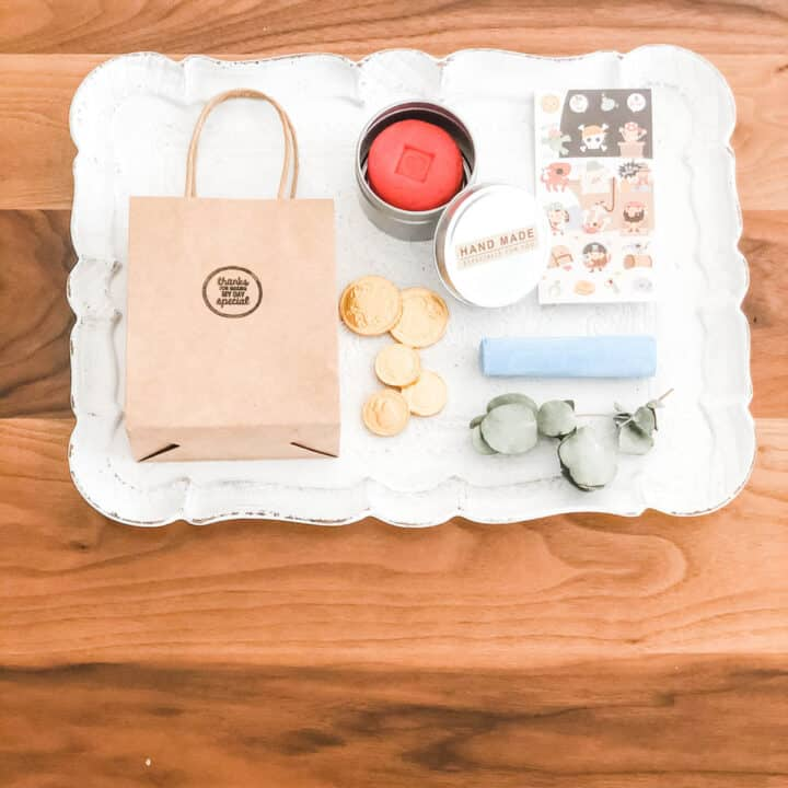 Image of a white tray on a timber table top with a flat lay arrangement of a brown paper bag with handle, tin with red play dough, gold chocolate coins, sheet of stickers, stick of blue chalk and dried leaves decoration