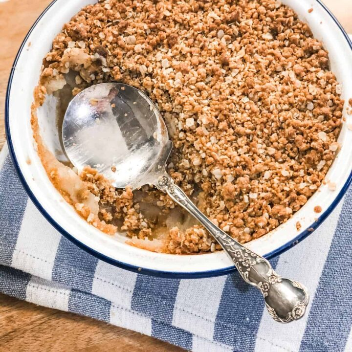 Close up image of a dish of apple crumble with a silver serving spoon set on a white and blue striped tea towel