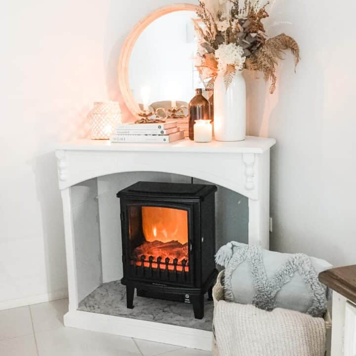 Image of a black faux fireplace hater in a white cabinet next to a basket with a cushion and throw rug and decorated with a round mirror, books, lantern candle and vase with dried florals
